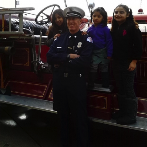 Three young girls stand behind a firefighter on an old fashioned fire truck